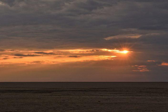 Sonnenaufgang am bewölkten Himmel über den Salzpfannen